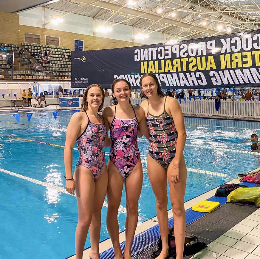 Alyssa Burgess and her two friends stand poolside at the Western Australia State Swimming Championships