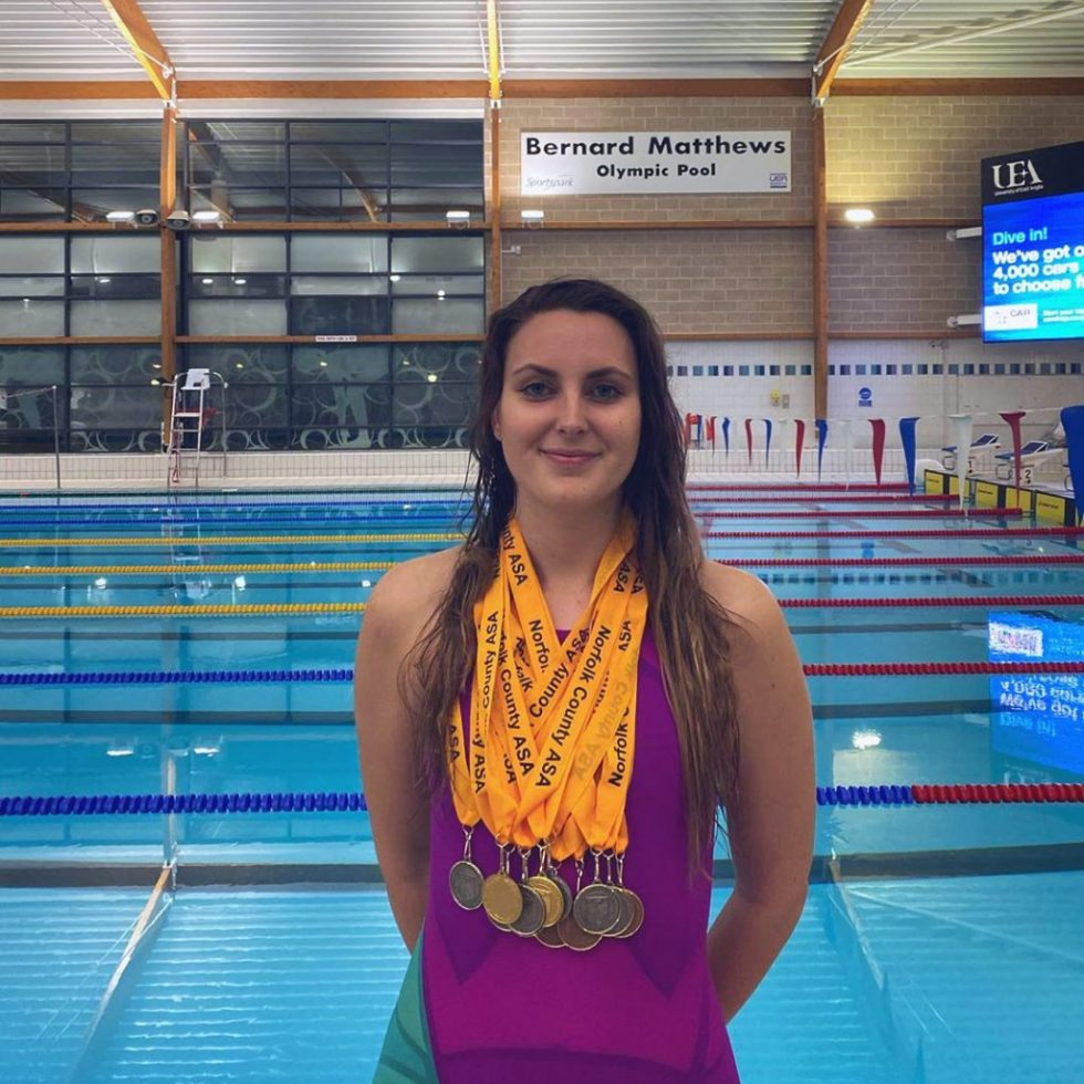Paralympic Swimmer Jessica-Jane Applegate stands poolside with a haul of medals around her neck