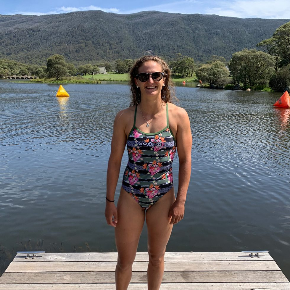 Penny Slater Stands Smiling by a lake in Snowy Mountains