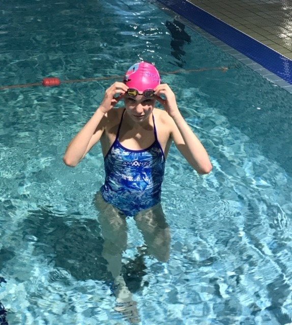 Deaf Swimmer Libby Gotta Adjusts her Swimming Cap and Goggles While In The Pool