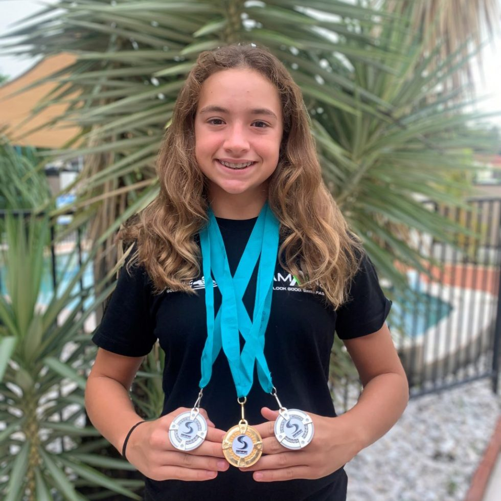 Micala shows off her AMANZI Squd t-shirt and x3 medals from a recent swimming meet