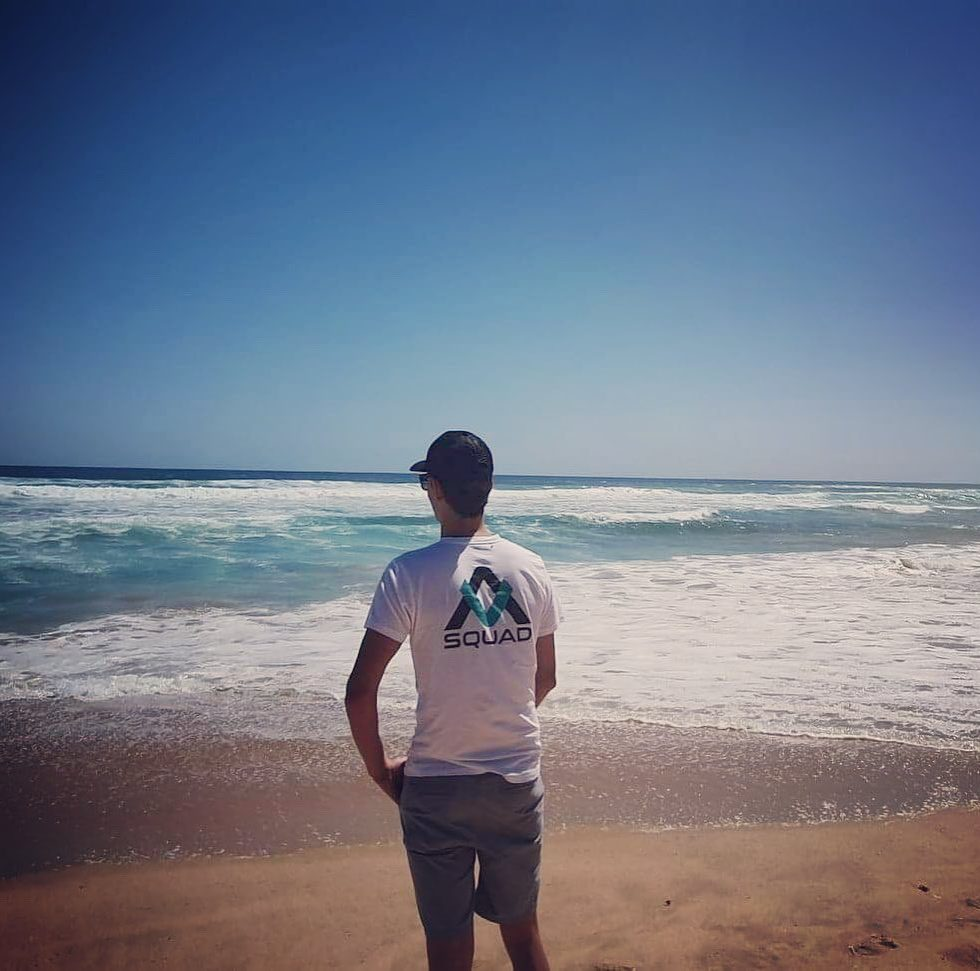 Matt Haanapple stands on the beach with an AMANZI shirt on, his back facing the camera,