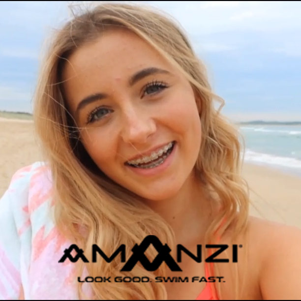 Young Swimmer Milly stands on a beach and smiles at the Camera as she takes a selfie.